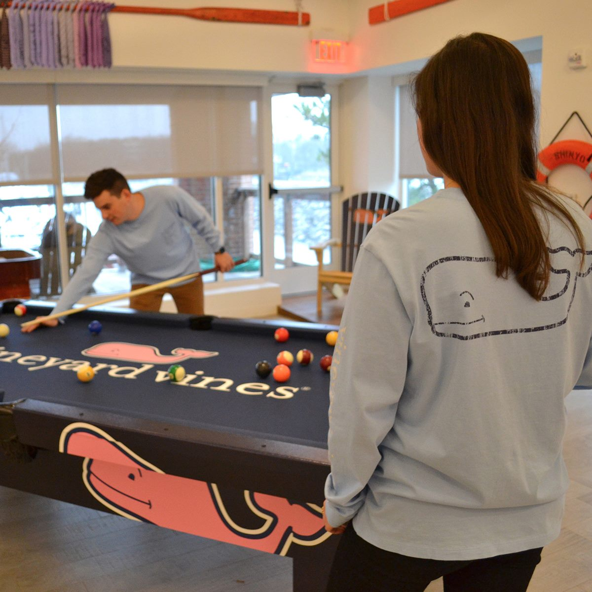 Two Vineyard Vines employees playing pool on a custom outdoor pool table by R&R Outdoors All Weather Billiards