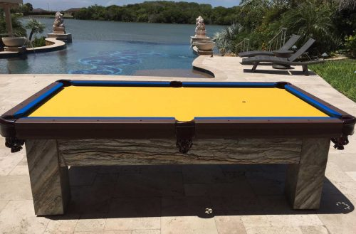 Blue and Yellow Artisan custom outdoor pool table sits pool side in client's Southwest Florida home
