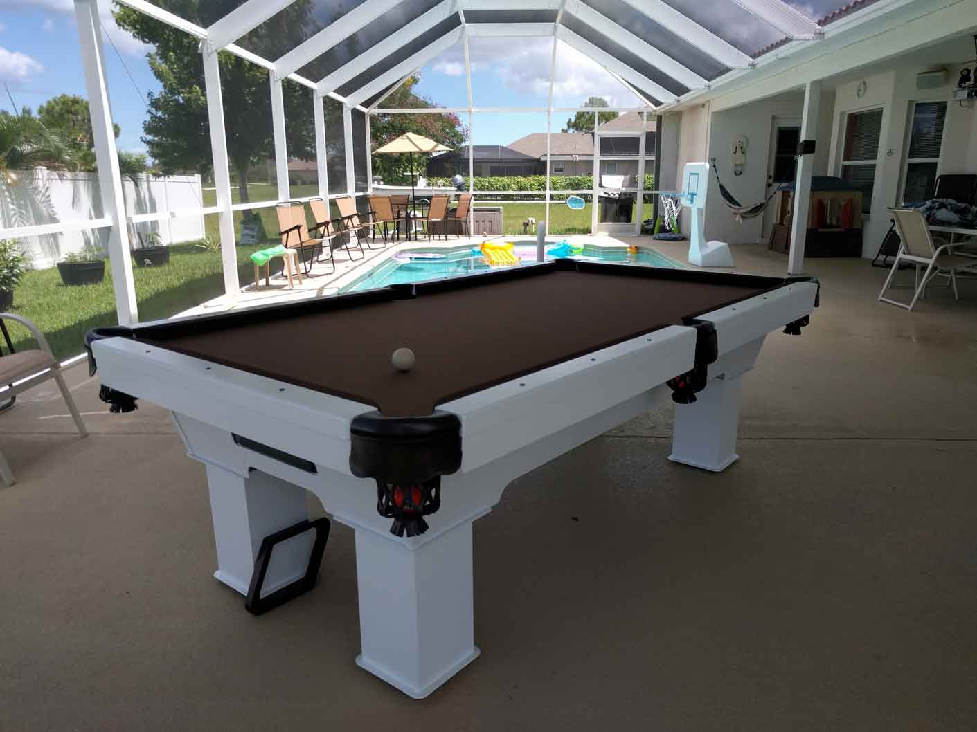 Brown and white Caesar outdoor pool table sitting poolside in a Southwest Florida Home