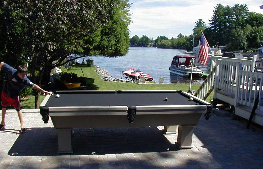 Client shooting pool lake front on Caesar custom outdoor pool table