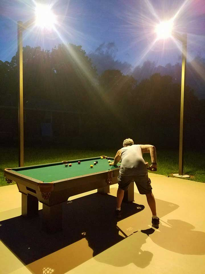 Client playing outdoors on custom built Caesar outdoor pool table by R&R Outoodrs