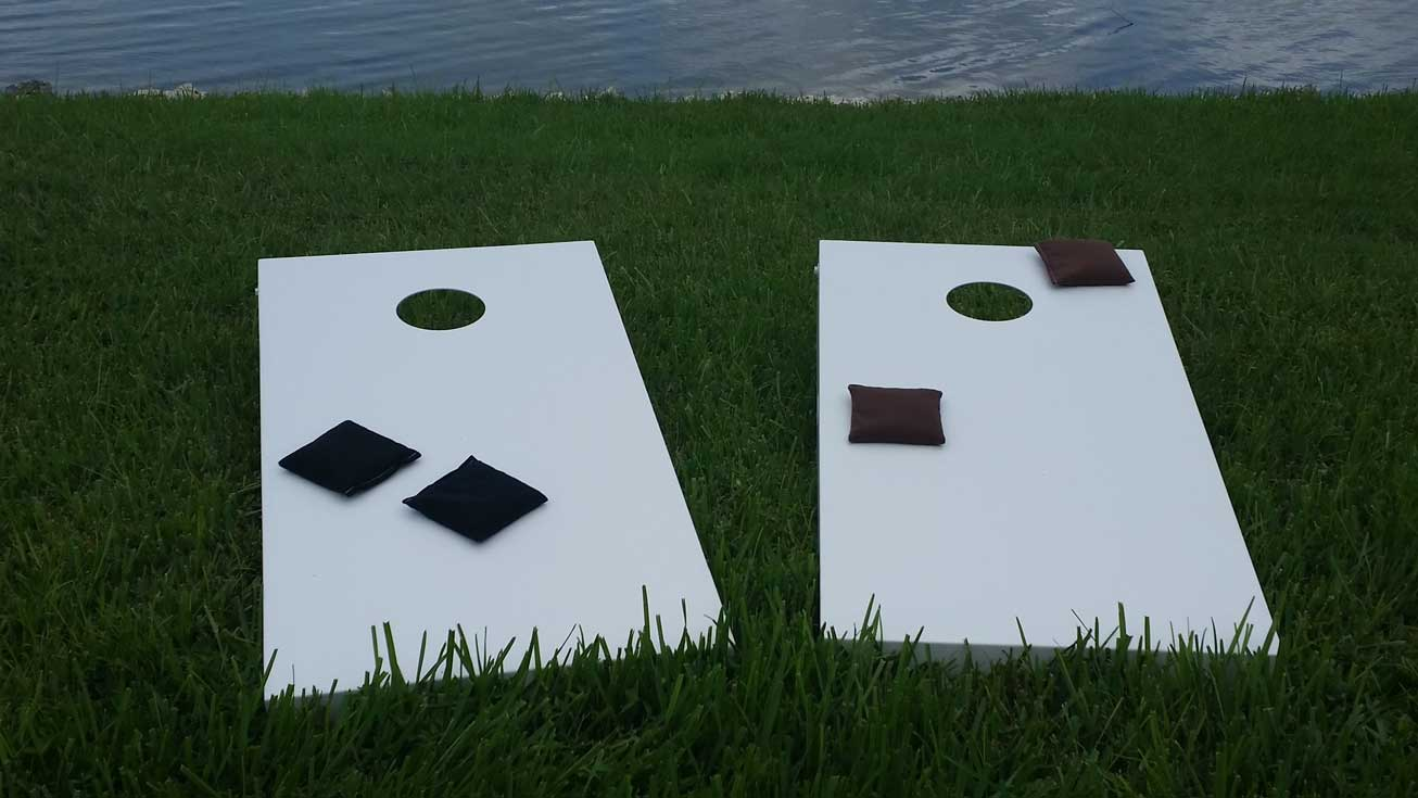 Outdoor cornhole game table set sits lakeside in client's Southwest Florida home