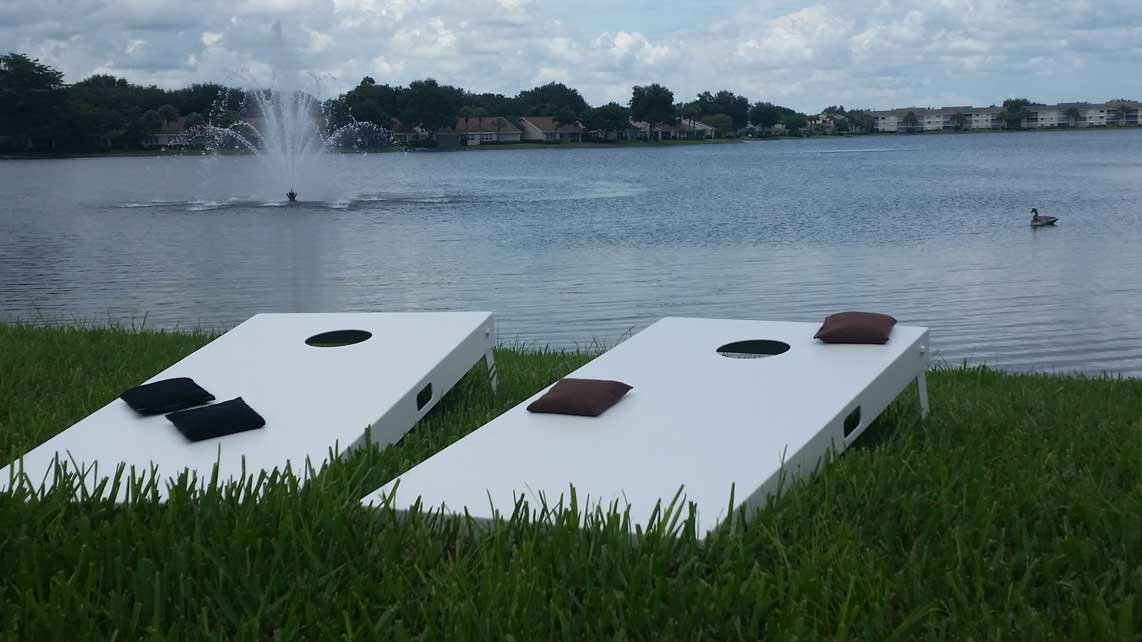 Outdoor cornhole set game table set sits lakeside in client's Southwest Florida home