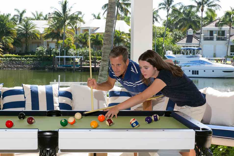 Father & daughter playing pool on an Oasis Outdoor Pool Table from R&R Outdoors, Inc.