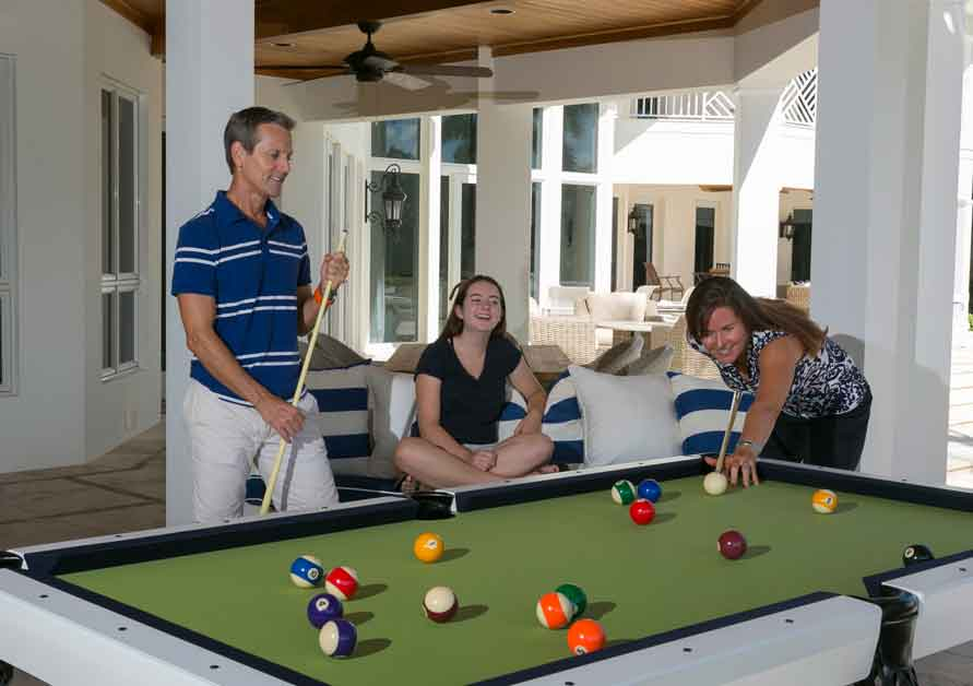 Family playing pool on Oasis Outdoor Pool Table from R&R Outdoors, Inc.