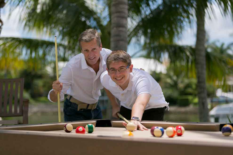 Father and Son enjoying their South Beach custom outdoor pool table from R&R Outdoors, Inc. All Weather Billiards
