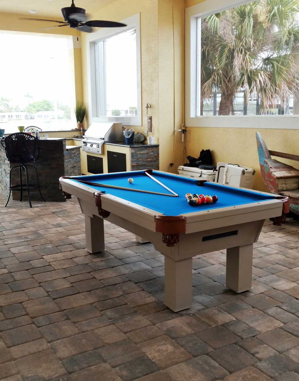 The Caesar, custom outdoor pool table, is the focal point of client's outdoor living space in Florida