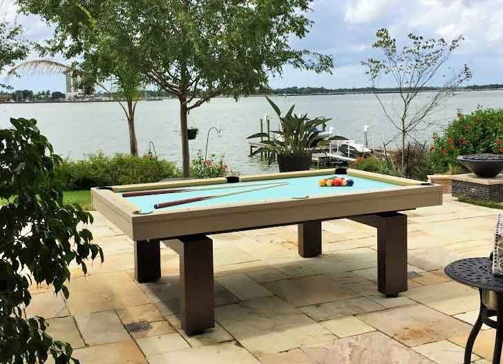 South Beach custom outdoor pool table by R&R Outdoors All Weather Billiards sits waterfront in Florida