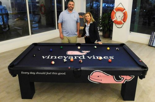 Robbie Selby and Shep Murray posing with Vineyard Vines customer Orion all weather pool table