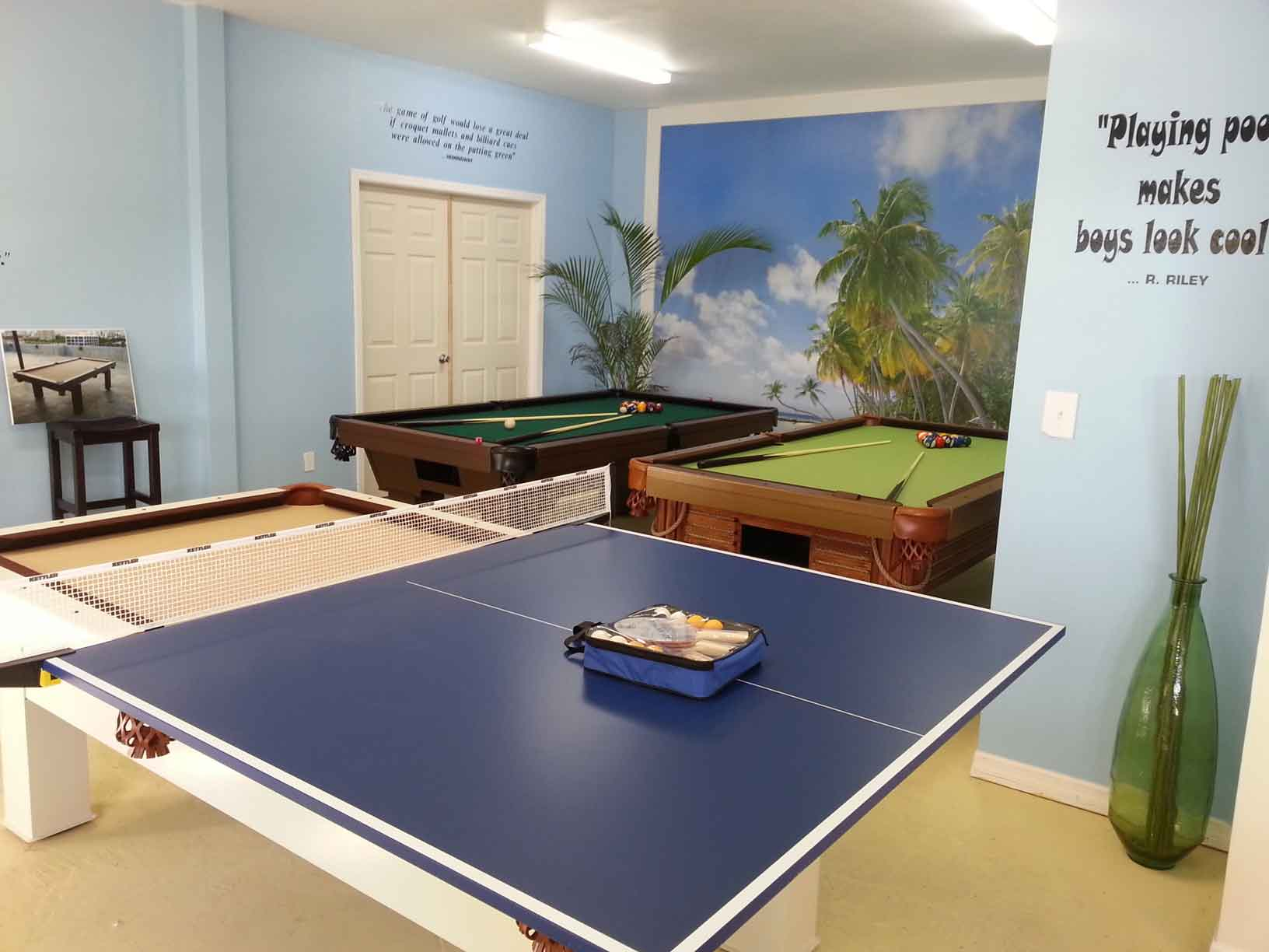 Assortment of outdoor pool tables and sample table tennis conversion top in R&R Outdoors All Weather Billiard showroom